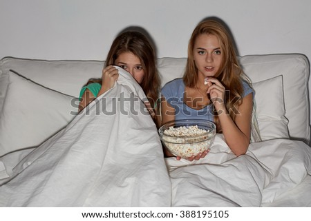 friendship, people, pajama party, entertainment and junk food concept - scared friends or teenage girls eating popcorn and watching horror movie on tv at home - stock photo