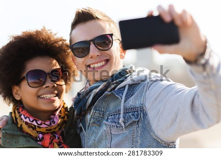 friendship, relations, tourism, travel and people concept - happy teenage friends or couple in sunglasses with smartphone taking selfie outdoors - stock photo