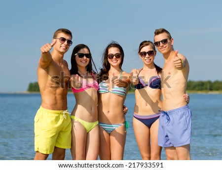 friendship, sea, holidays, gesture and people concept - group of smiling friends wearing swimwear and sunglasses showing thumbs up on beach