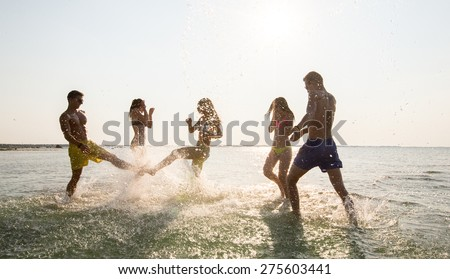 friendship, sea, summer vacation, holidays and people concept - group of happy friends having fun on summer beach - stock photo