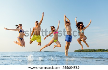 friendship, sea, summer vacation, holidays and people concept - group of smiling friends wearing swimwear and sunglasses jumping on beach - stock photo