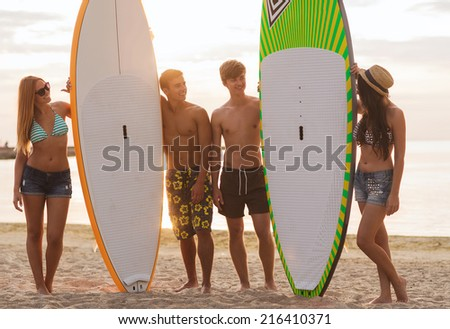 friendship, sea, summer vacation, water sport and people concept - group of smiling friends wearing swimwear and sunglasses with surfboards on beach - stock photo