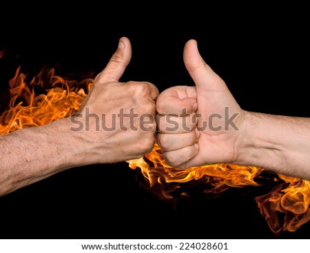 Friendship sealed with fire concept. Two men bumping fists with thumbs up against the fire flames - stock photo