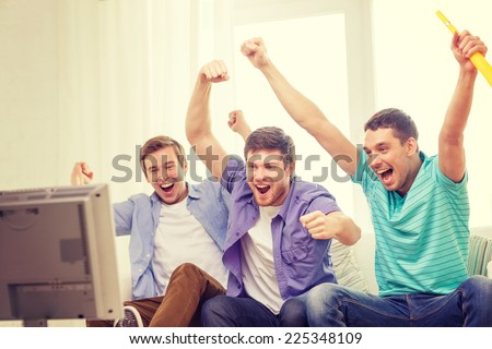 friendship, sports and entertainment concept - happy male friends with vuvuzela watching sports on tv - stock photo