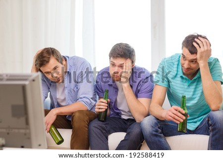 friendship, sports and entertainment concept - sad male friends with beer watching sports on tv at home - stock photo