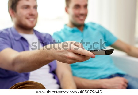 friendship, sports, people and entertainment concept - close up of happy male friends with remote control watching tv at home