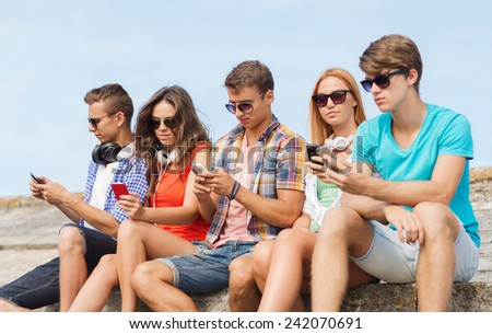 friendship, summer, technology and people concept - group of friends with smartphones and headphones outdoors - stock photo