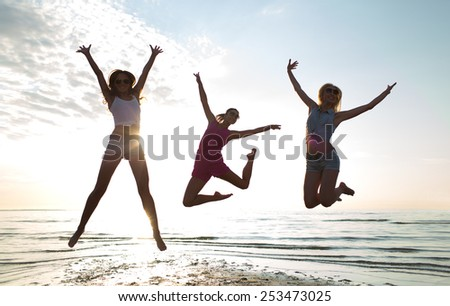 friendship, summer vacation, freedom, happiness and people concept - group of happy female friends dancing and jumping on beach - stock photo