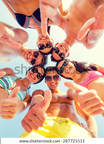 friendship, summer vacation, holidays, gesture and people concept - group of smiling friends wearing swimwear standing in circle and showing thumbs up over blue sky