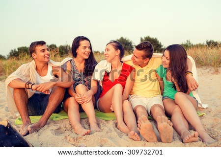 friendship, summer vacation, holidays, gesture and people concept - group of smiling friends sitting on beach