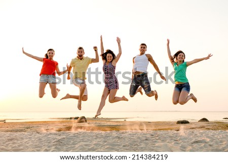 friendship, summer vacation, holidays, party and people concept - group of smiling friends dancing and jumping on beach - stock photo