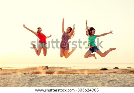 friendship, summer vacation, holidays, party and people concept - group of smiling teen girls jumping on beach - stock photo