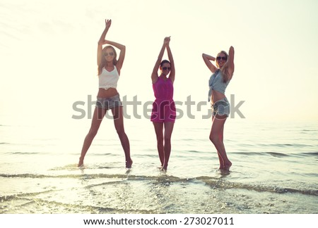 friendship, summer vacation, party, happiness and people concept - group of happy female friends dancing on beach - stock photo