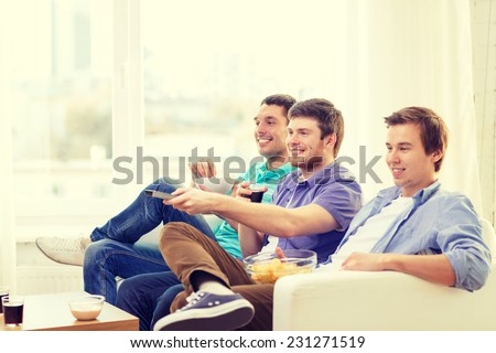 friendship, technology and home concept - smiling male friends with remote control and junk food at home - stock photo