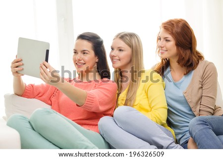 friendship, technology and internet concept - three smiling teenage girls taking picture with tablet pc computer camera at home