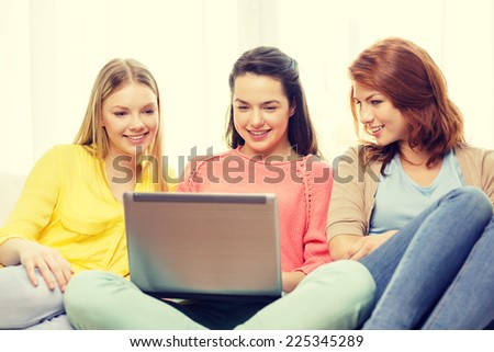 friendship, technology and internet concept - three smiling teenage girls with laptop computer at home - stock photo