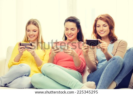 friendship, technology and internet concept - three smiling teenage girls with smartphones at home - stock photo
