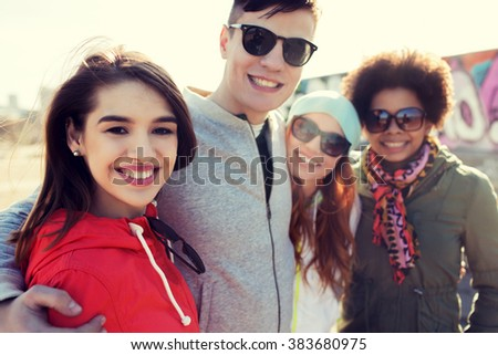 friendship, tourism, travel and people concept - group of happy teenage friends in sunglasses hugging outdoors