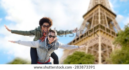 friendship, travel, tourism and people concept - happy international teenage couple in shades having fun over paris eiffel tower background - stock photo