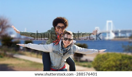 friendship, travel, tourism and people concept - happy international teenage couple in shades having fun over rainbow bridge at tokyo in japan background - stock photo