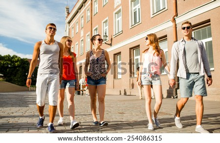friendship, travel, tourism, summer vacation and people concept - group of smiling teenagers walking in the city - stock photo