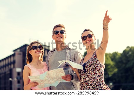 friendship, travel, tourism, vacation and people concept - smiling friends with map and city guide pointing finger outdoors - stock photo