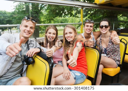 friendship, travel, vacation, summer and people concept - group of happy friends with digital camera traveling by tour bus and showing thumbs up - stock photo