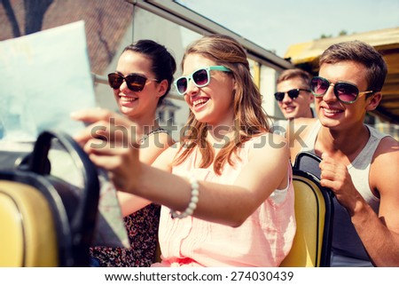 friendship, travel, vacation, summer and people concept - group of smiling friends with map traveling by tour bus - stock photo