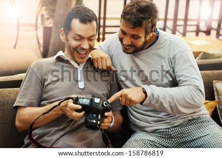Friendship - two friends looking at photos in camera - stock photo
