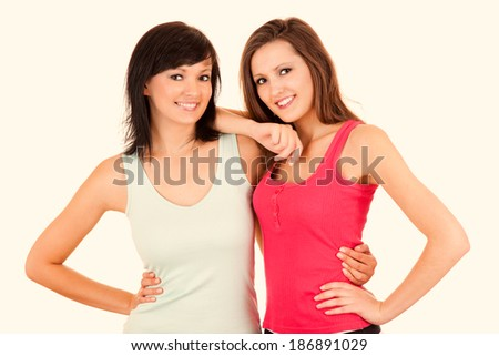 Friendship - Two girlfriends hugging each other, white background - stock photo