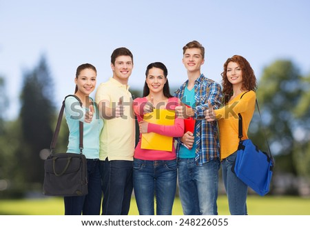 friendship, vacation, education, gesture and people concept - group of smiling teenagers with folders and school bags showing thumbs up over park background - stock photo