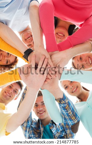 friendship, youth and people concept - group of smiling teenagers with hands on top of each other - stock photo