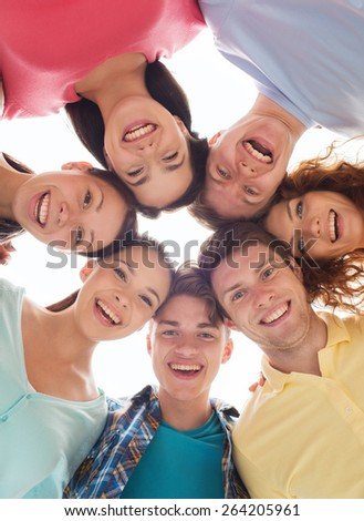 friendship, youth and people - group of smiling teenagers in circle - stock photo