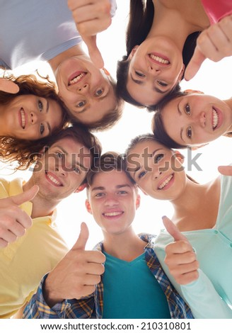 friendship, youth, gesture and people - group of smiling teenagers in a circle showing thumbs up - stock photo