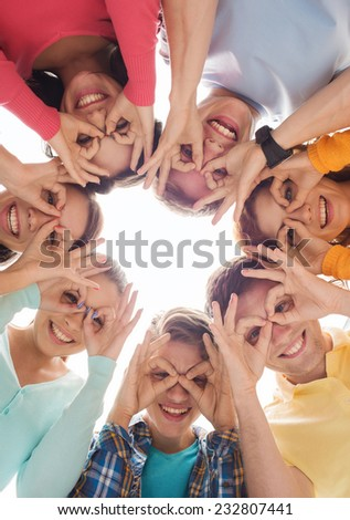 friendship, youth, gesture and people - group of smiling teenagers in circle having fun
