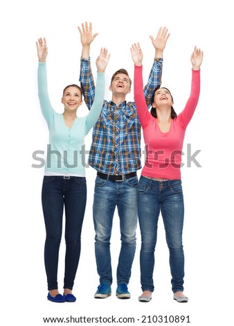 friendship, youth, greeting and people - group of smiling teenagers with raised hands