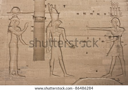 Frieze on the wall of Egypt's Philae temple: Pharaoh's offering to the Gods Horus and Hathor - stock photo