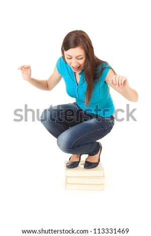 frightend young woman squat on the pile of books, white background - stock photo