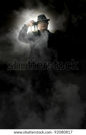 Frightened And Spooked Senior Man Walking Around A Foggy Cemetery At Midnight With A Lit Up Lantern When Working The Graveyard Shift - stock photo