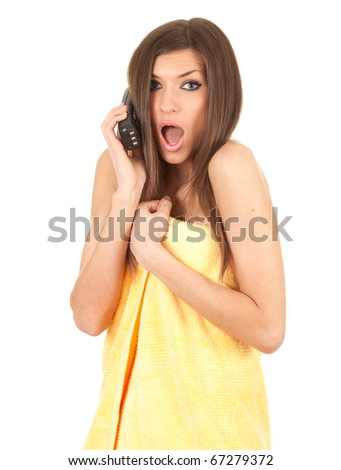 frightened beautiful young woman in yellow towel speaks by a mobile phone - stock photo