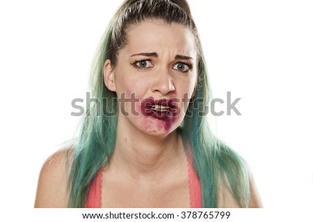 frightened beautiful young woman with smeared lipstick
