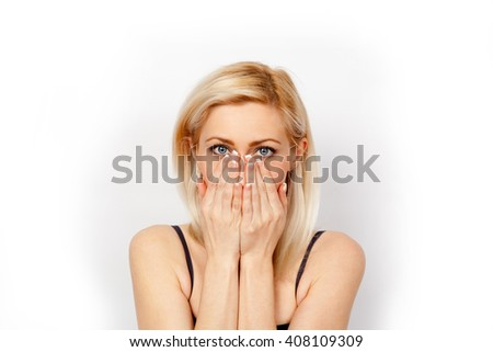 Frightened blond girl covers her face with her hands - stock photo