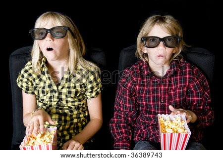 Frightened Boy and Girl Wearing New Style 3-D Glasses in a Movie Theater - stock photo
