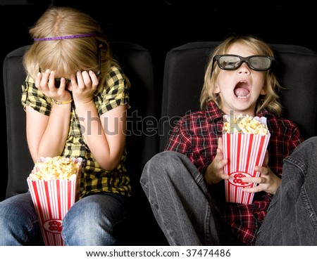 Frightened Boy and Girl Wearing New Style 3-D Glasses in a Movie Theater