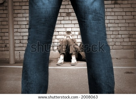 frightened boy at the school yard and a mans legs - stock photo