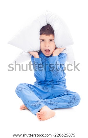 Frightened boy covers his ears with a pillow and screams - stock photo