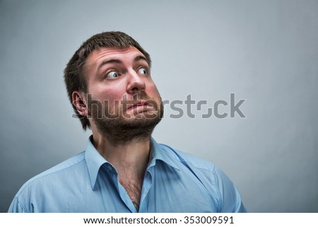 Frightened businessman wearing blue shirt over grey - stock photo