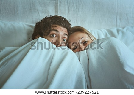Frightened couple with eyes wide open under the sheets. Fear and shock concept - stock photo