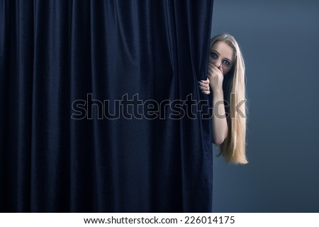Frightened girl hiding behind a curtain. - stock photo