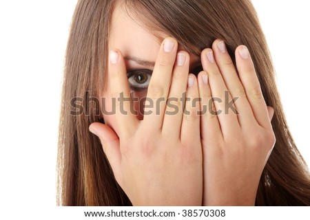 Frightened girl hiding her face behind her hands isolated on white background - stock photo